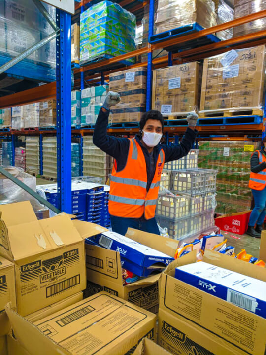 Foodbank Victoria staff member in a triumphant pose, their fists in the air