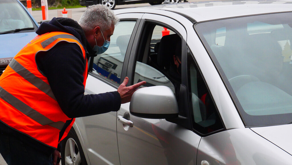 CEO of Foodbank Victoria, Dave McNamara, talking to a person in their vehicle