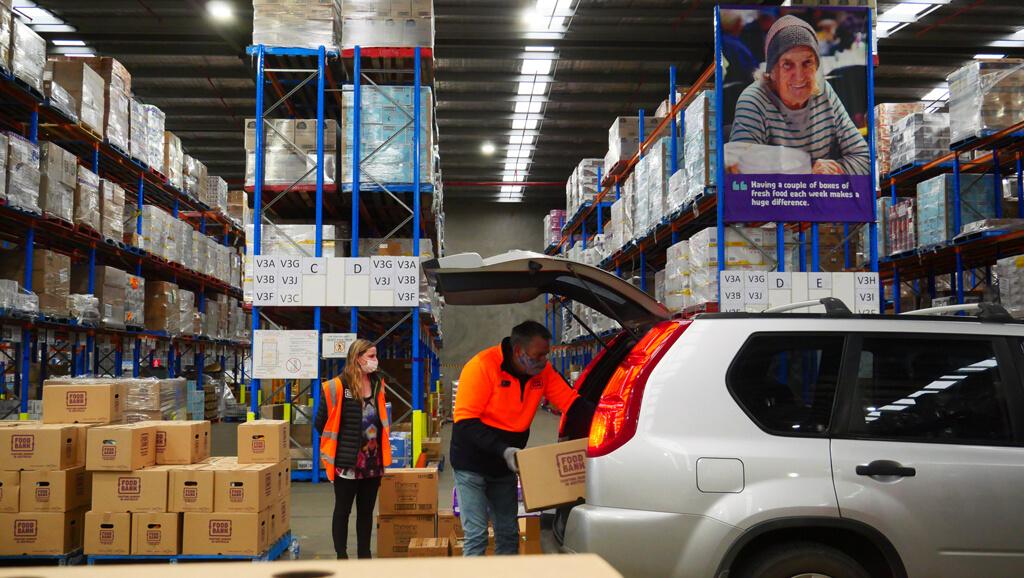 Volunteer loads a car with a Foodbank hamper